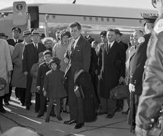 President John F. Kennedy, arriving at Chicago's O'Hare Airport, is greeted by his niece Maria Shriver, 5, holding on to his coat, and Bobby, 6, his nephew, and Kennedy's sister, Eunice Shriver, walking just behind the president, April 28, 1961. (AP Photo)