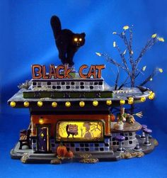 """Halloween Black Cat Diner by Snow Village Halloween. $275.00. Halloween collectible. Dept 56 ceramic house. out of print. """"Black Cat Diner"""" Dept. 56 Snow Village Halloween Gift set of 4, Item #55319. Limited to year production 2003. Mint condition in original box & sleeve. Building outside lights flash. Includes """"You Go First"""" accessory, 10"""" tree, leaves, & 3V adaptor.  Box has several rip in the top, but all display items in mint condition."""