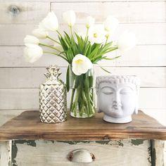 Luxury decor pieces for the home. White flower arrangement ideas. Wooden table decor ideas. Silver pieces of home decor. Buddha inspired home decor. White home decor inspiration. White and silver home decor pieces.