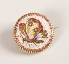 A micro mosaic circular brooch depicting a butterfly with ribbed edging to the frame