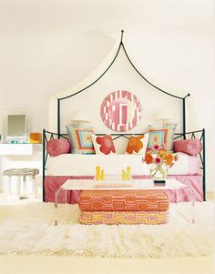 The black wrought-iron daybed in this bedroom by designer Sally Henderson, can be used as both a sofa and bed. A Lucite Crisp coffee table from the Conran Shop sits atop a Pottery Barn Teen flokati rug. The chessboard is by Karim Rashid, from the MoMA shop. All fabrics are from the Designers Guild through Osborne & Little.   - HouseBeautiful.com