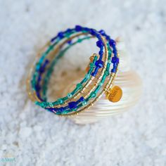 Inspired by the beautiful tropical beaches and golden sands of Tahiti, this handmade spiral bangle is made with radiant 22K Gold Plated beads, beautiful glass crystal beads and fine glass seed beads in shades of turquoise, royal blue and gold.