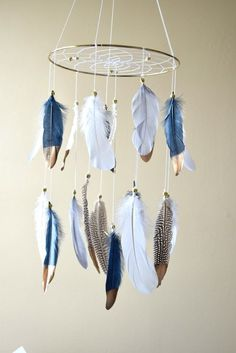 This gorgeous natural feather dreamcatcher mobile will make all your dreams come true :) This mobile can be hung beside a crib, changing table, rocking chair, perfect for a baby boy/ girl nursery, Native American style or tribal bedroom decor. Features made of a sturdy gold metal hoop 10 in diameter. Webbed with white cotton string and a few gold crystal beads on the web. The gold dipped snow white, navy blue, grey and natural color pheasant feathers are attached by gold pony beads. The…