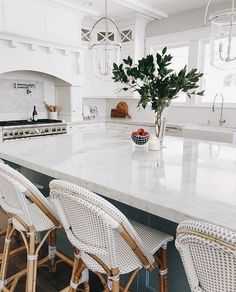 Pretty white kitchen home design decor inspiration ideas. White marble countertops, big marble island with white wicker bar stools chairs, viking stove and pot filler, pretty Hamptons style light fixtures. Decor, Furniture, Interior, Home Decor, House Interior, Home Kitchens, Home Bar Accessories, Interior Design, Gorgeous White Kitchen