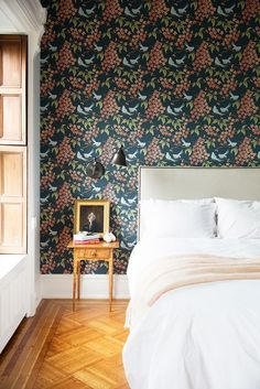 Bird and floral patterned wallpaper in bedroom with neutral headboard and bedding, and a small wooden side table.