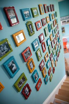 wall of black and white photos in cheap colored frames
