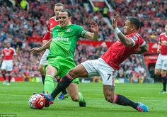 Former United defender John O'Shea (left) stretches for a 50/50 challenge with United forward Memphis Depay