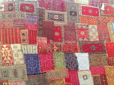 The colourful rugs lined with patterns are lied out next to each other to look like a repeated pattern itself.
