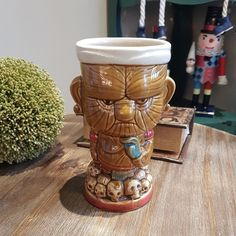 Headhunter Tiki Mug, standing on a pile of his trophies.