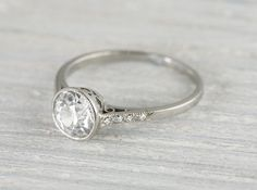 This refined Art Deco vintage engagement ring is made in platinum and centered with an approximate 1.03 carat EGL certified european cut diamond with G color and VS1 clarity. Circa 1920 Center diamond is elegantly set inside a bezel setting featuring faint millegrain edges. Beautiful narrow thin band. Feels effortless on the finger, perfect for everyday wear.Learn more about Art Deco rings Diamond and gold mining has caused devastation in areas such as Africa, wreaking havoc on delicate eco...