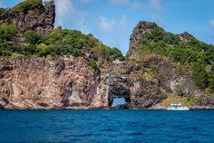 """Ponta da Sapata. Não é uma região para banhos. Nessa ponta da ilha principal, está a vegetação nativa da ilha, não mexida por ser uma região íngreme e não habitada. Uma abertura, de lado a lado, na falésia, é chamada de """"portão"""" e, de alguns ângulos, assemelha-se ao mapa do Brasil. É um dos lugares preferidos pelos mergulhadores."""