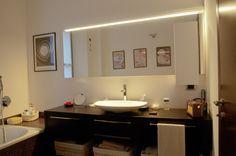 Illuminazione della zona lavandino con barra a led posizionata sopra lo specchio.