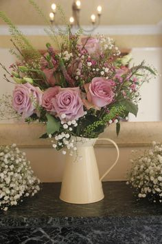 Purple wedding flowers, roses, gypsophelia and love the white pitcher
