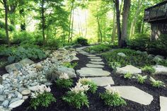 via DiSabatino Landscaping. Dry creek bed alongside stone path. Shade garden.