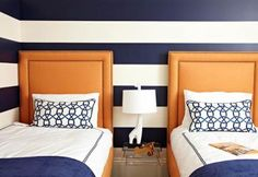 Bright orange headboards stand out against the thick navy-and-white striped walls in a young boy's room. - Traditional Home ® / Photo: Werner Straube / Design: Melissa Warner