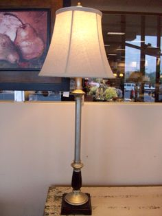 This slender buffet lamp has a silver finish tubing with a canvas shade,and a dark walnut finish base. This small lamp gives off a lot of light and is a perfect accessory to a small space