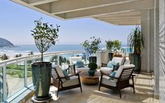 A cor das almofadas harmoniza com o azul do mar, assim como a cerâmica celadon, em tons de verde. A madeira em tora combina com o tom do piso. Foto: Divulgação