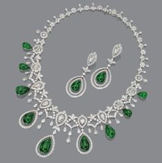 DIAMOND AND EMERALD NECKLACE AND EARRINGS.  The graduated necklace of lace design set with 18 rose-cut diamonds and numerous round diamonds supporting a fringe of 9 emerald drops, the matching pendant earclips set with 2 rose-cut and numerous round diamonds and with 2 emerald drops mounted in 18 karat white gold, necklace length 16 inches.