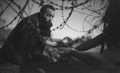 Primer premio del WPP 2016: Autor Warren Richardson. La esperanza en una nueva vida. Un hombre pasa a su bebé entre el alambre de púa en la frontera entre Serbia y Hungría. Foto: vía Reuters