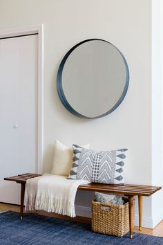 In the entryway, a rounded mirror hangs above a midcentury modern slatted bench…