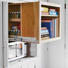 "This slide-out storage cube holds cookbooks in the front and a built-in spice rack in the rear. A small microwave in the cubby below is usually hidden behind the cabinet's ""flipper"" doors, which open out into the room and then slide back neatly into recesses along the sides."