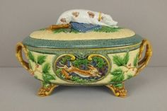 "MINTON majolica large size ""Gun Dog"" game dish with hunting dog on cover with gun, game bag and shot pouches of bed of ferns, base has a running rabbit on one side and a game bird on the other, paw feet and vine handles"
