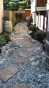After installing foot drains around the house, the sand-set flagstone patio was sloped toward a decorative drain grate and a drainage swale was installed, doubling as a path. Wine casks serve as rain barrels, collecting storm water from drainspouts.