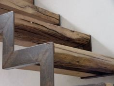 Recycled, Up-cycled or Re-used - These stairs are derived from the no longer usable old roof beams of the original home. But the visual punch comes from the oxidized iron L-profiles which have been laid as the edging of the treads and risers.