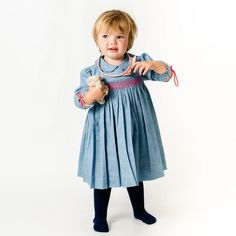 We just love this sweet delicate baby blue and white dotted print dress. It has long sleeves with a frilled cuff, hand smocked pink detail on the bodice, a rounded collar with pink embroidery and comes with a pair of matching bloomers.