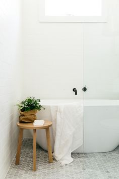 Bathroom with subway tiles, marble hexagon mosaic tile floor with white grout. Cross Street by CM Studio. Photo by Carolin McCredie.