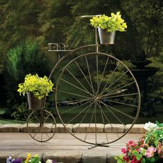 "Old Fashioned Bicycle Plant Stand - Vintage charm is in bloom! This adorable planter's frame looks like a high-wheel bicycle from bygone days, with one large wheel in the front and a smaller wheel in back. Attached are three pails that are ready to hold your blooming plants. This lovely accessory will look great on your patio or in your favorite room. Made from iron. Plants not included. Some assembly required. Dimensions: 33¾"" tall x 32"" long x 10"" wide"