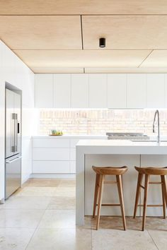All white kitchen, with subtle warm walls, floor and ceiling.