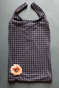 used tank top re purposed into a tote bag. As easy as turning inside of sewing all edges and turning right side out again. Hot glue a cute flower to decorate it :)