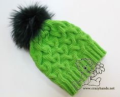 Green cable knit hat for winter with dark green raccoon fur pom pom