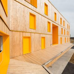 Doors, windows and recesses are picked out in yellow ochre on the timber facade…