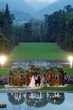 As dusk falls, the bride and groom exchange vows under a flower- laden altar. As...