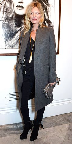 Kate Moss in black separates (including her favorite suede boots), grey coat, and ivory pendant necklace, paired with metallic clutch.