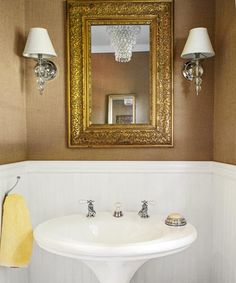 Task lighting in the bath shouldn't come from overhead, as it casts unflattering shadows. Better option: create a cluster of lighting, with overall ambient illumination coming from a small chandelier, pendant, or flush-mounted fixture on the ceiling, and task lighting provided by a pair of dimmable wall sconces set at eye level on either side of the mirror. | Photo: Helen Norman