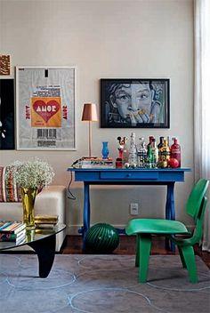 Herança de família, a escrivaninha de madeira antiga recebeu pintura automotiva na cor azul Bic e virou um apoio para bebidas na sala do apartamento. Um banner que imita uma embalagem de paçoca é a alegria da parede.