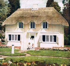 """. Triang """"Princess Elizabeth"""" Dolls House, No.6518, 1930's, modelled on Princess Elizabeth's (now Queen Elizabeth II) """"Y Bwthyn Bach"""" (The Little House). A cottage playhouse, still standing in the grounds of the Royal Lodge Windsor. Thatched effect roof and stuccoed exterior, opens at front to reveal 4 rooms, hall, staircase and landing, imitation linoleum flooring, fireplaces, bath and sink, wired for light, print curtains and metal opening windows, 24""""/61cm x 30""""/76cm x 17""""/43cm."""