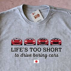 """This edition of the """"Life's Too Short to Drive Boring Cars"""" shirt features an all red lineup of the iconic Miata. The NA, NB, NC, and the brand spanking new ND. • Supremely soft 90/10 heather blend •"""