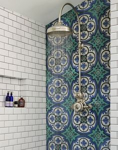 Mediterranean-inspired bathroom in a Victorian terrace house, South-West London. Walk-in shower with Drummonds Dalby Shower with curved arm. Mediterranean floor tiles in sea blues and greens from Rustico Tile & Stone.