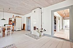 Bielone deski podłogi biegnące prostopadle do drzwi wydłużają perspektywę mieszkania. Zestawiono je przekornie z surowym drewnem na suficie. Zachowany piec kaflowy wpisuje się idealnie w rustykalny wystrój salonu i jadalni z drewnianym stołem oraz starymi krzesłami.