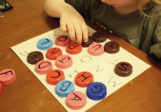 Practicing letter recognition with milk caps