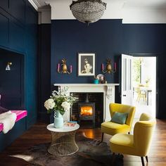 The fireplace, the pineapple sconces, the yellow and pink velvet, the deep navy walls - so much to list after in this incredible living room. Shot by @paulraeside #livingroom #darkwalls #bluewall #velverchair #velvet #interiordesign #chandelier