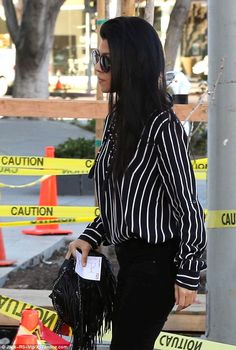 Hot mom: Kourtney looked fab in a pair of jet black skinny jeans, with a thick black and white pin-striped blouse and black heeled ankle boots