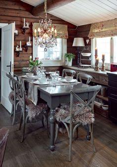 LUN HULE: Kjøkkenet er svart og møblene er grå, likevel føles ikke kjøkkenet mørkt, men derimot intimt og koselig. Vegglamper, bordlamper og levende lys gir en intim stemning. Spisebordet er kjøpt på salg i Sandefjord, men saget til i ny høyde og malt av hytteeierne. Spisestolene er fra Home and Cottage. Fargen på bordet og stolene er Jotun Supreme Finish, Elegant. Tømmerveggene er beiset i Sjøsand, Jotun interiørbeis. Taket er malt i fargen Kritthvit.