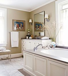 Create a natural focal point in a master bathroom by placing a tub beneath a window. Repeating materials throughout the space elevates style and helps to move the eye throughout the space. Sophisticated soapstone dresses the countertop and borders the floor tile./