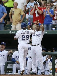 Texas Rangers Adrian Beltre is greeted at the top of the dugout by Elvis Andrus, right, and bench coach Steve Buechele, bottom left, after Beltre hit a solo home run off of San Diego Padres starting pitcher Ian Kennedy during the fourth inning  Friday, July 10, 2015, in Arlington, Texas. (AP Photo/Tony Gutierrez)