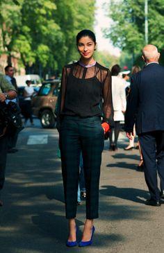 Caroline Issa. sheer black blouse. dark green trousers. cobalt shoes.